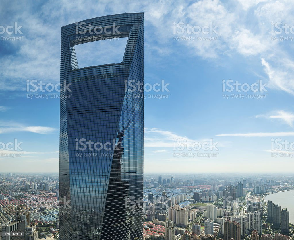 Corporate blue glass skyscraper soaring above city below stock photo