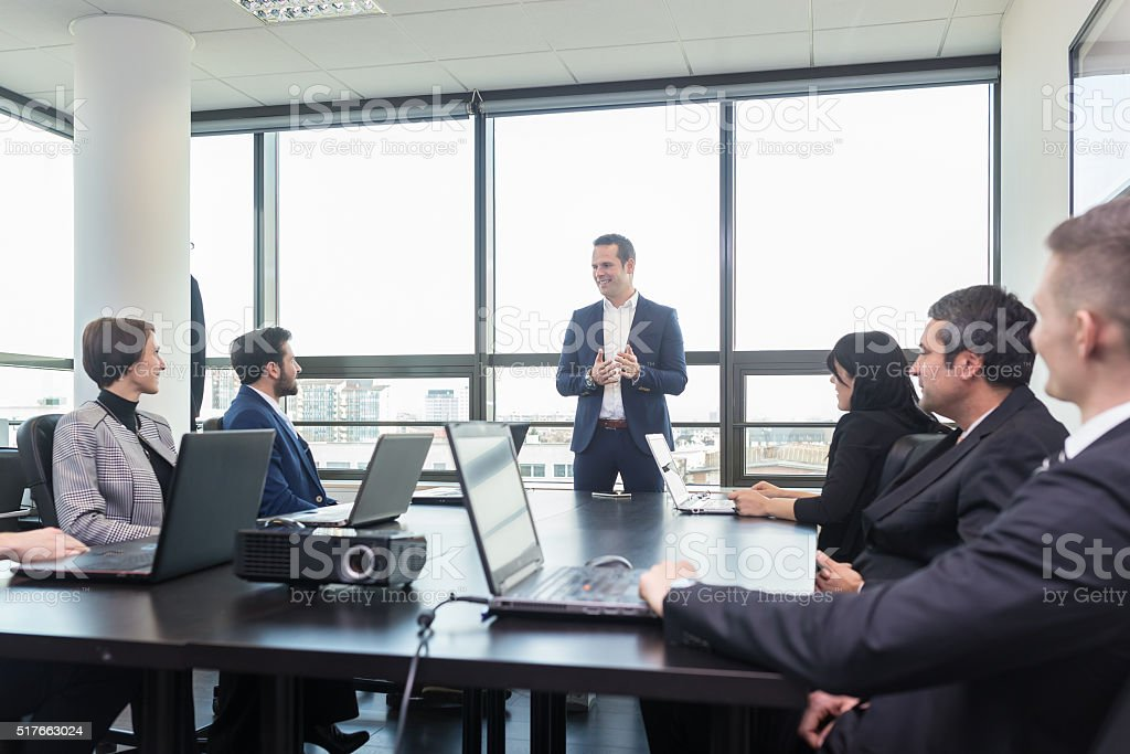 Corporate business team office meeting. Successful team leader and business owner  leading in-house business meeting, explaining business plans to his employees. Business and entrepreneurship concept. Adult Stock Photo
