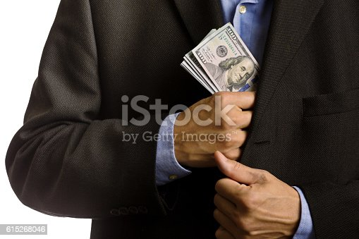istock Corporate Businessman Slipping U.S. dollars Money into Suite Pocket 615268046