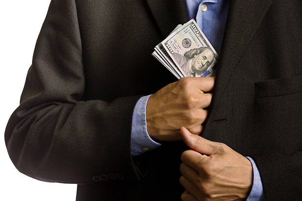 corporate businessman slipping u.s. dollars money into suite pocket - pocket stock photos and pictures