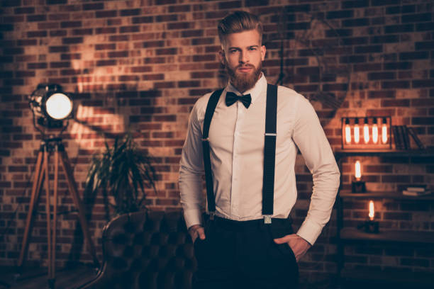 Corporate chic posh concept. Portrait of brunette elegant graceful handsome stunning groomed serious focused concentrated rich wealthy guy keeping hands in pockets standing over brick background Corporate chic posh concept. Portrait of brunette elegant graceful handsome stunning groomed serious focused concentrated rich wealthy guy keeping hands in pockets standing over brick background suspenders stock pictures, royalty-free photos & images