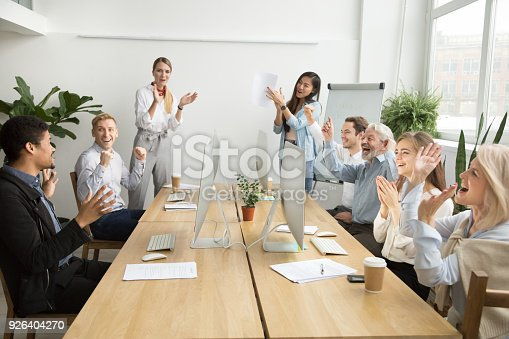 istock Corporate diverse team congratulating african coworker with business success applauding 926404270