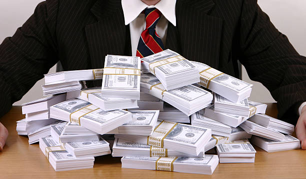 Corporate Greed Suit behind stacks of prop money. greed stock pictures, royalty-free photos & images