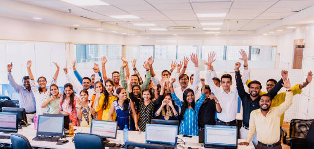 Corporate Group Portrait of Cheering Staff Members Corporate Business, Indian, Office - Large Group of Cheerful Business Executives Looking at the Camera for a Group Portrait at their office call centre photos stock pictures, royalty-free photos & images