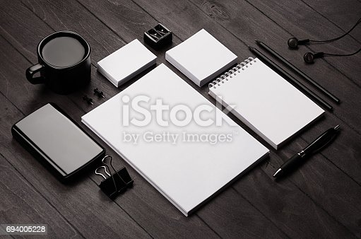 istock Corporate identity template,  blank stationery set with coffee and earphone on black stylish wood background. Mock up for branding, business presentations and portfolios. 694005228