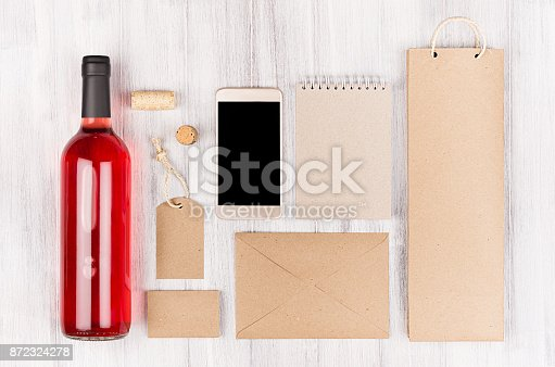 istock Corporate identity template for wine industry,  blank beige kraft packaging, stationery, phone set with bottle rose wine on soft white wood background. 872324278