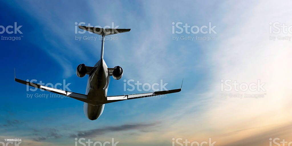 corporate jet airplane flying at dusk stock photo
