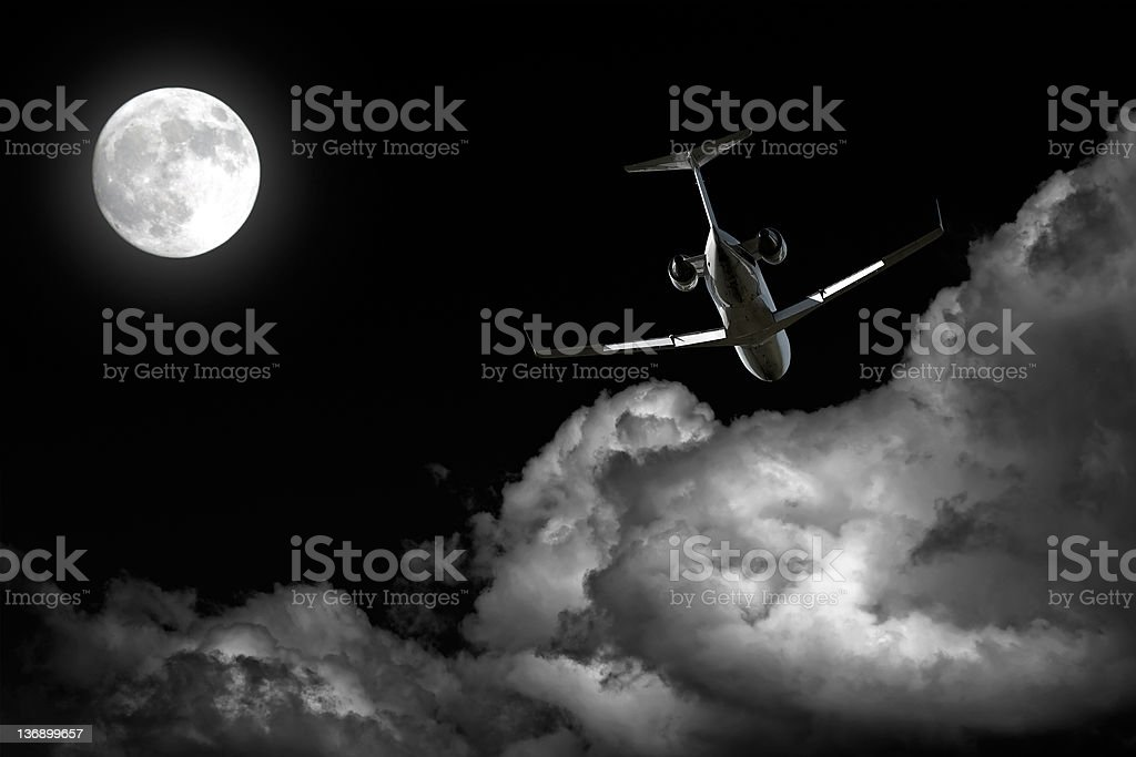 corporate jet airplane flying at night stock photo