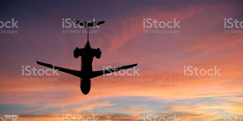 corporate jet airplane flying at sunset stock photo