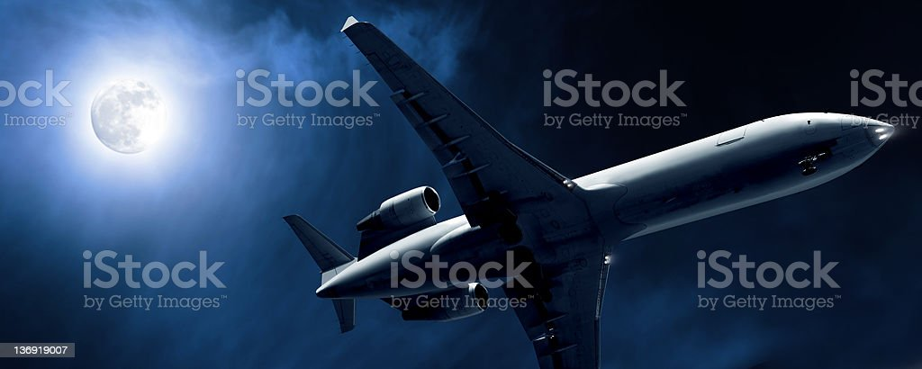 corporate jet airplane landing at night stock photo