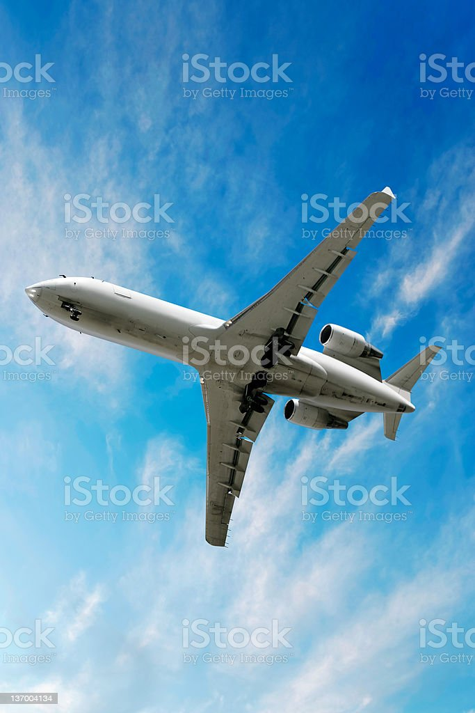 XXL corporate jet airplane landing in bright sky royalty-free stock photo