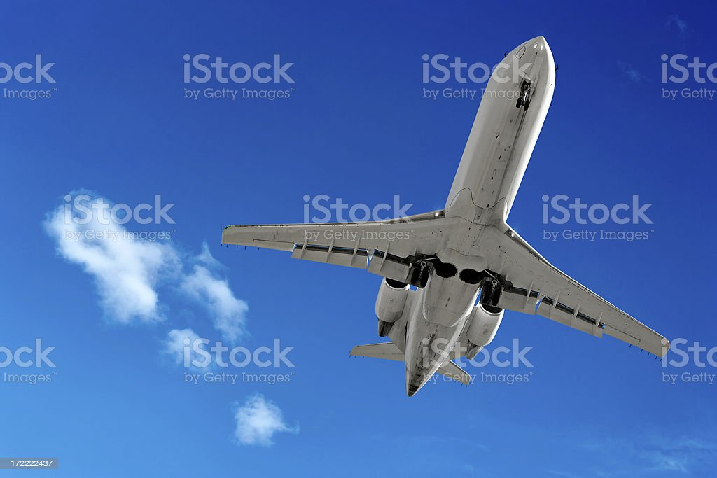 corporate jet airplane landing in bright sky royalty-free stock photo
