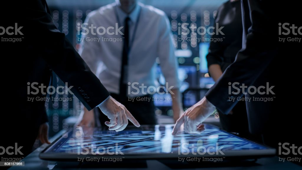 Corporate Managers Working at the Table in Monitoring Room. Room is Full of State of the Art Technology. Computers with Animated Screens. stock photo