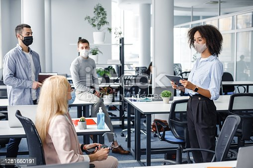 Corporate meeting and group work in modern company in office interior. African american woman manager in protective mask holding tablet, talking to workers keeping social distance during epidemic