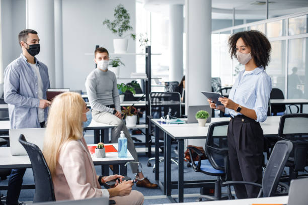 Corporate meeting and group work in company. African american woman manager in protective mask holding tablet, talking to workers keeping social distance stock photo