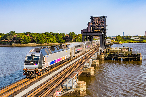 Rutherford, United States – August 9, 2017: Bombardier NJ Transit commuter train with state-of-the-art dual-powered Bombardier ALP-45DP locomotive #4504 and bilevel (Multi-level, double-decker) Bombardier stainless steel cars crossing the HX Drawbridge over the Hackensack River enroute to Suffern.  In the background is the World Trade Center tower. The bascule bridge built in 1911 carries both the Bergen County and Pascack Valley lines.  Horizontal, copy space.