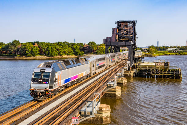 Corporate NJ Transit Bombardier commuter train crossing Hackensack River bridge Rutherford, United States – August 9, 2017: Bombardier NJ Transit commuter train with state-of-the-art dual-powered Bombardier ALP-45DP locomotive #4504 and bilevel (Multi-level, double-decker) Bombardier stainless steel cars crossing the HX Drawbridge over the Hackensack River enroute to Suffern.  In the background is the World Trade Center tower. The bascule bridge built in 1911 carries both the Bergen County and Pascack Valley lines.  Horizontal, copy space. bascule bridge stock pictures, royalty-free photos & images