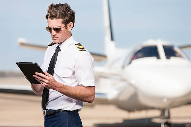 corporate pilot using electronic tablet - pilot stock photos and pictures