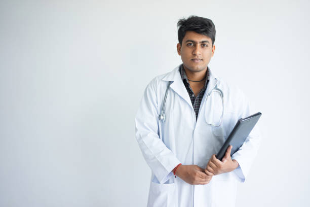 Corporate portrait of young physician holding folder stock photo