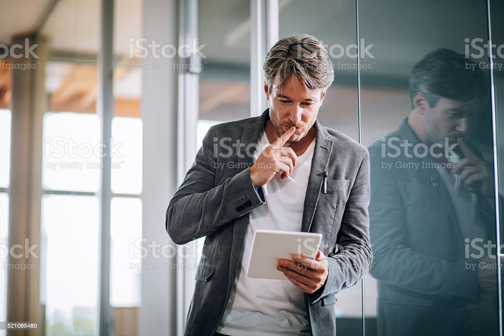 Corporate professional executive concentrating on a presentation on his tablet. stock photo
