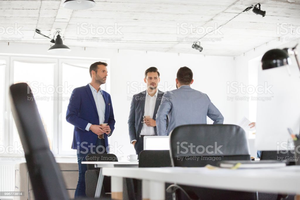 Corporate professionals discussing during coffee break Corporate professionals discussing during coffee break in office. Group of business associates talking during a break in office. Adult Stock Photo