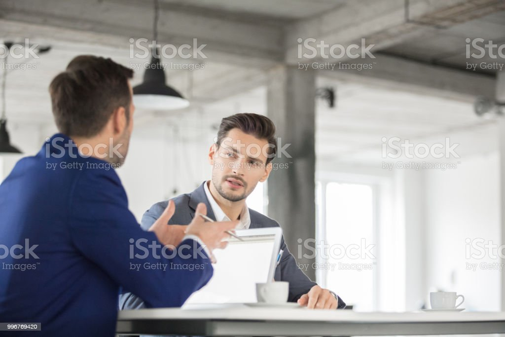 Corporate professionals discussing new business plan Young entrepreneur listening to the suggestions of coworker during a meeting. Corporate professionals discussing new business plan in meeting. Adult Stock Photo