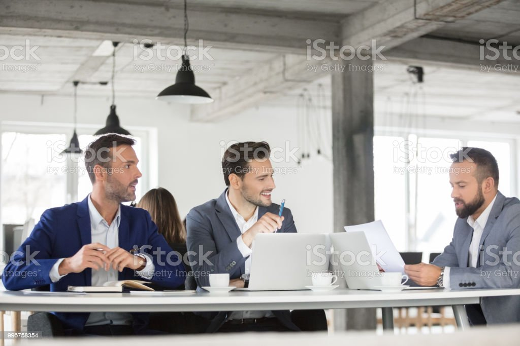 Corporate professionals discussing over a contract in meeting Team of corporate professionals discussing over a document in meeting. Group of business people brainstorming in meeting. Adult Stock Photo