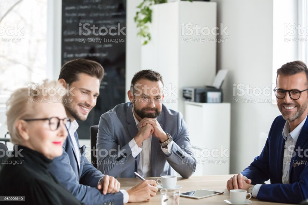 Corporate professionals during a staff meeting Group of professionals looking at a colleague giving presentation. Corporate professionals during a staff meeting in office. Adult Stock Photo