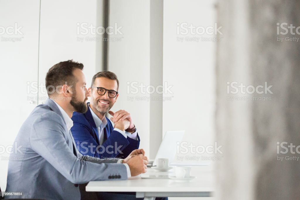 Corporate professionals during meeting Smiling businessman listening to the discussion during meeting. Businesspeople meeting in office boardroom. Adult Stock Photo