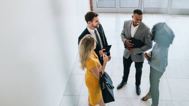 Corporate professionals having casual meeting in office lobby Group of young business professionals standing together and having casual discussing in office hallway. Business colleagues having casual meeting in office lobby. jacoblund stock pictures, royalty-free photos & images
