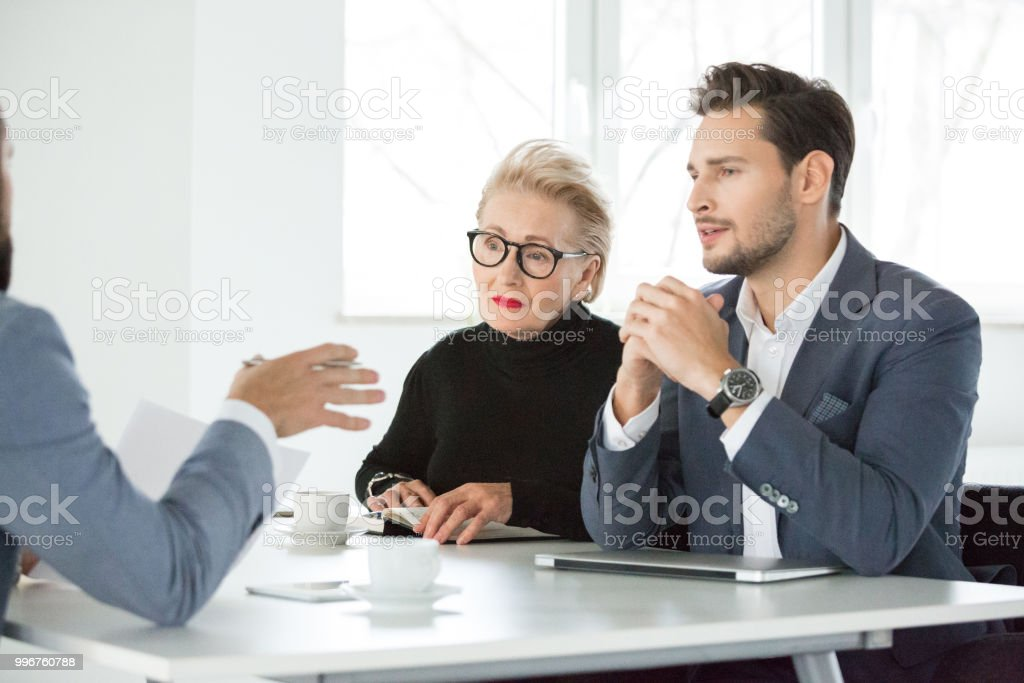 Corporate professionals having meeting in office Business people listening to a colleague in meeting. Corporate professionals having meeting in office. Active Seniors Stock Photo