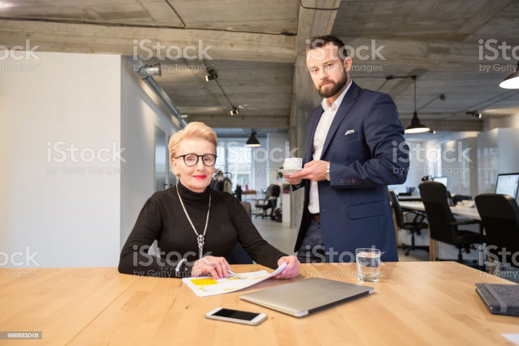 Corporate professionals in office Business man and woman at office looking at camera Active Seniors Stock Photo
