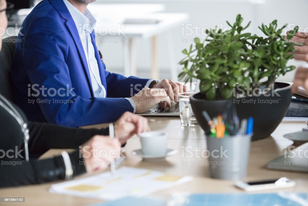 Corporate professionals sitting at meeting table Corporate business people sitting at table in office space. Team of professionals during meeting in office. Adult Stock Photo