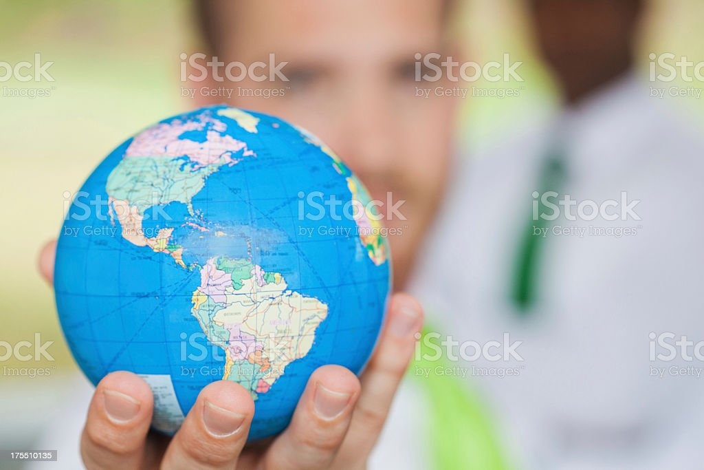 Corporate responsibility; business man holding globe; environmental issues; selective focus royalty-free stock photo