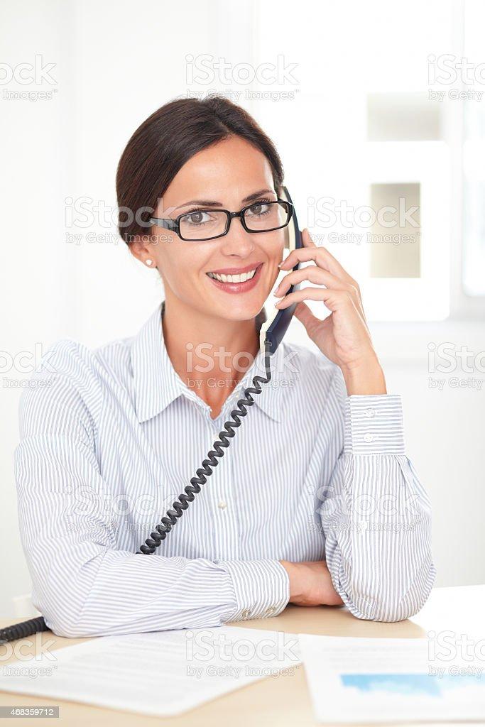 Corporate secretary happily talking on the phone royalty-free stock photo