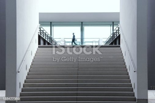 Staircase in modern architecture leading to light window facade with corporate person rushing by