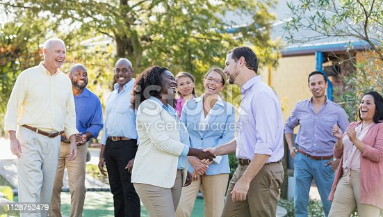 A multi-ethnic group of nine business people participating in corporate team building activities, standing outdoors.  The coworkers range in age from 20s to 60s. The focus is on the young African-American woman, in her 20s, and the mid adult man, in his 30s, standing with her in the foreground. They are shaking hands as their colleagues watch.