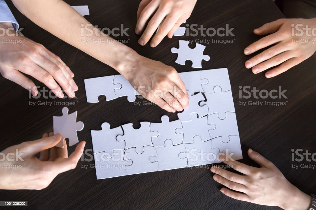 Corporate team people collaborating connecting puzzle on desk working...