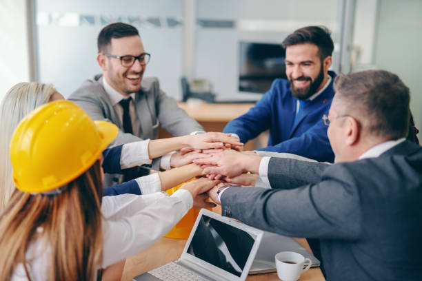 Corporate team stacking hands while sitting at desk at boardroom. Replace the fear of the unknown with curiosity. Corporate team stacking hands while sitting at desk at boardroom. Replace the fear of the unknown with curiosity. labor union stock pictures, royalty-free photos & images