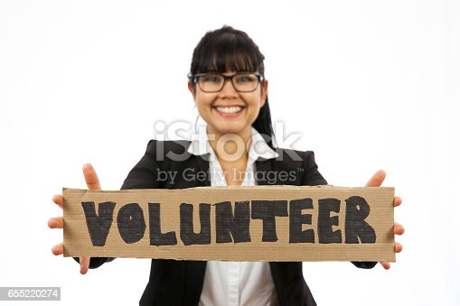 Businesswoman dressed in a suit and holding a sign which says VOLUNTEER. Studio shot on a white background.