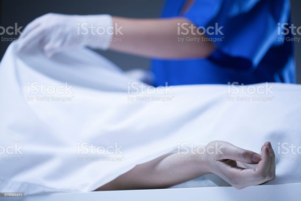 Corpse covered by sheet stock photo