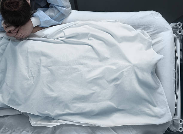 Corpse in a hospital bed and suffering woman stock photo