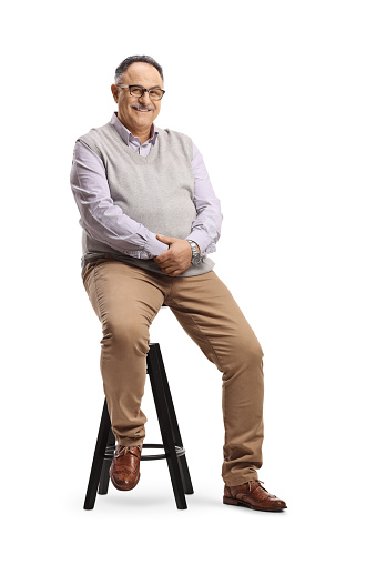 Corpulent mature man sitting on a high chair isolated on white background