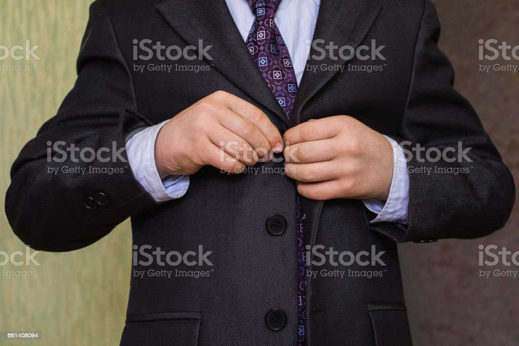 correct button on jacket, hands close-up, dressing, man's style, correcting sleeves,  boy preparing for the school royalty-free stock photo