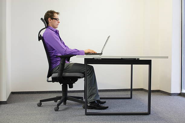 correct sitting position at laptop in ofice stock photo