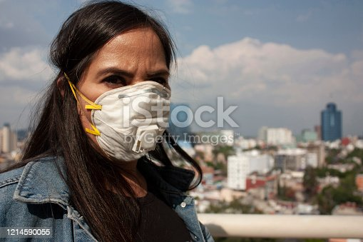 istock Correct use covers mouths to avoid transmitting contagions due to viral or bacterial diseases. Long-haired Mexican woman background Mexico city between 40 and 45 years 1214590055