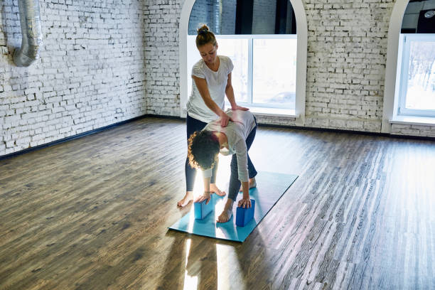 Correcting spine at yoga class stock photo