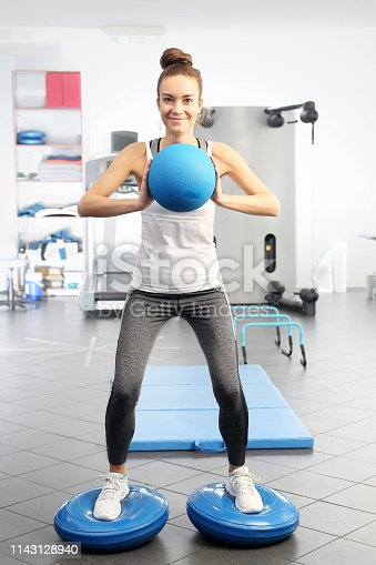 Gym training. A young woman is training on with a training ball in an exercise room.