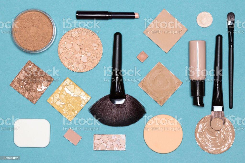 Corrective makeup flat lay set on blue surface stock photo