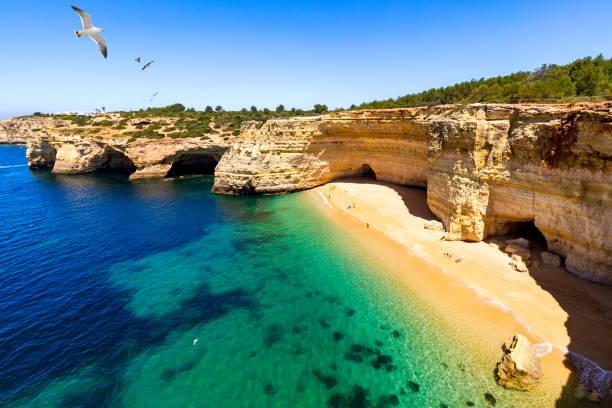 Corredoura Beach, gesichteter Aussichtspunkt auf den Spuren der Sieben abgehängten Täler (Sete Vales Suspensos). Praia da Corredoura mit fliegenden Möwen in der Nähe von Benagil Dorf, Algarve, Portugal. – Foto
